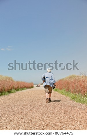 Single senior man walking on path to the beach on hot summer day with clear blue sky. - stock photo