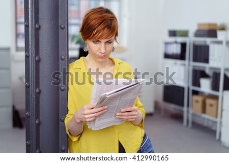 Single serious businesswoman in casual shirt and jeans leaning on column while reading a newspaper at her small office - stock photo
