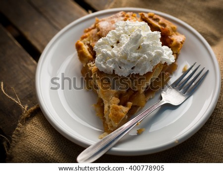 Single slice of apple pie with whipped cream and fork sitting on wooden surface. - stock photo