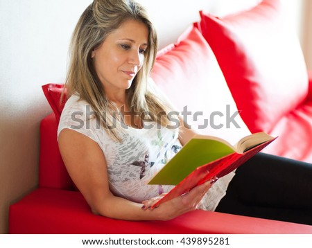 Single smiling gorgeous mature woman in white blouse reading a hard cover book while relaxing on red sofa indoors - stock photo