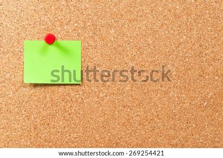 Single sticky note green on cork board horizontal - stock photo