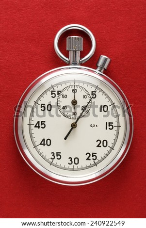 Single stopwatch closeup on red paper background - stock photo