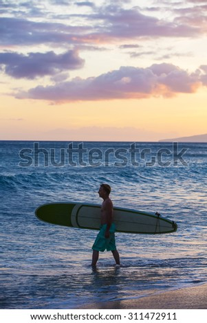 Single surfer carrying his surfboard into the ocean