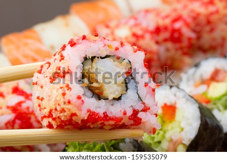 Single sushi roll in tempura with red tobiko and in chopsticks with background on sushi made dish - stock photo