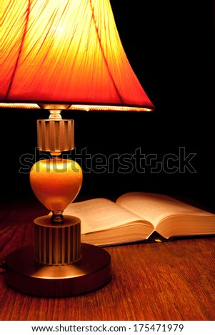 Single table-lamp and opened book in the dark room