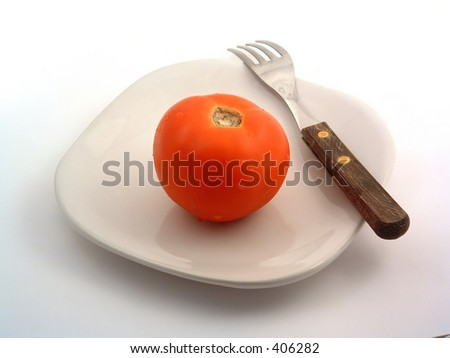 single tomato on a plate and fork - stock photo