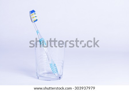 Single toothbrush in glass representing oral dental hygiene and concepts of being single and lonely - stock photo
