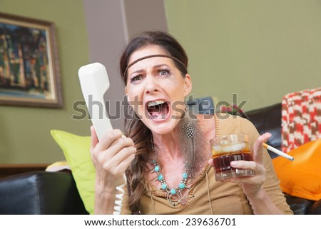 Single upset female with drink and cigarette yelling into phone - stock photo