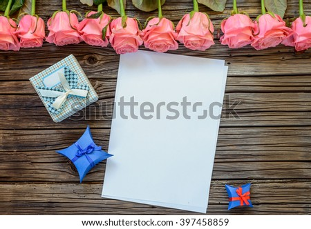 Single vertical sheet of blank white paper in between three little Valentines Day gift boxes below row of stemmed pink roses over wooden background - stock photo