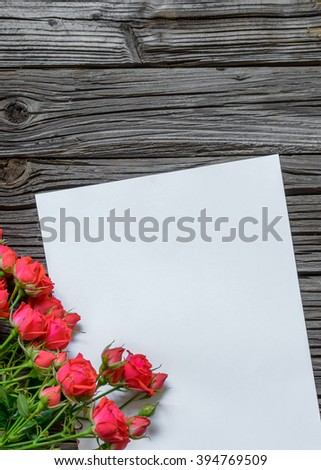 Single white blank paper with copy space on table with weathered wooden surface next to bundle of stemmed pink roses in corner - stock photo