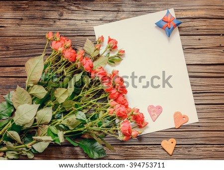 Single white blank sheet of paper with copy space on table with weathered wooden surface next to bundle of pink roses, heart shapes and little gift box - stock photo