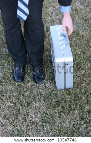 Single white businessman bends over and reaches for metal briefcase - stock photo