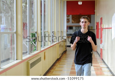Single white Caucasian male young adult walks through his school hallway with his hands on his backpack straps. - stock photo