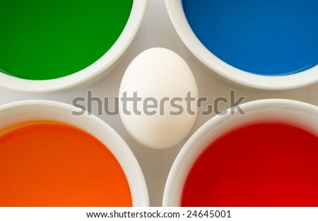 Single white egg surrounded by colorful dyes - stock photo