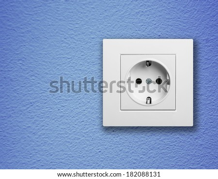 single white electric socket on blue wall  - stock photo