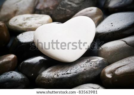 Single white heart on black pebble stones,  still life. - stock photo