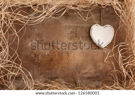 single white heart on grunge wooden background with straws - stock photo