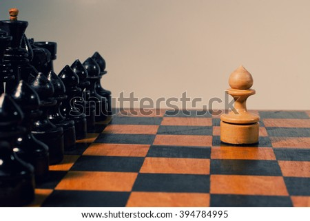 Single white pawn and rows of black chess figures on an old chessboard (retro style) - stock photo