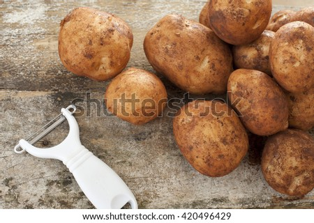 Single white plastic and metal peeler next to piles of raw yellow potatoes on top of old wooden table - stock photo
