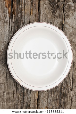 single white plate on old wood background - stock photo