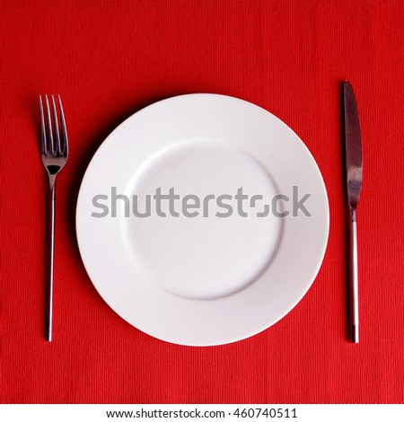 Single white round plate with cutlery on red