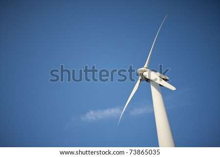 Single Wind Turbine Over Dramatic Blue Sky and Clouds. - stock photo