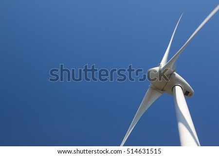 Single Wind Turbine producing alternative energy. Against a clear blue sky.