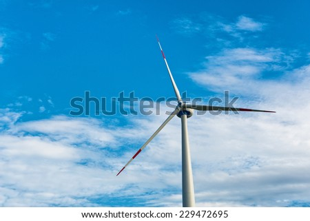 Single wind turbine providing sustainable energy and electricity by converting the kinetic energy of the wind using a natural resource against a blue sky with copyspace - stock photo