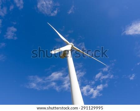 Single wind turbine stopped in blue sky - stock photo