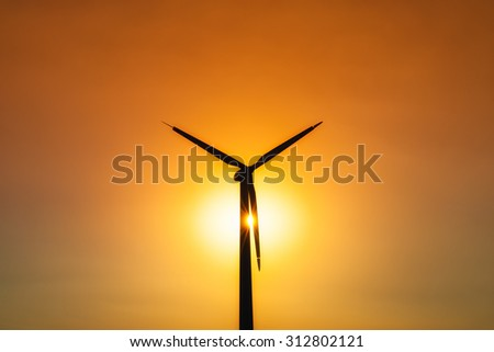 single wind turbine sunset background concept ecosystem for design - symmetrical composition - stock photo