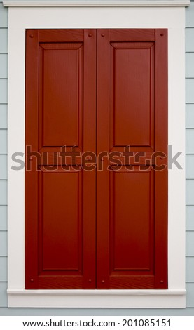 Single window protected by red wooden shutters - stock photo