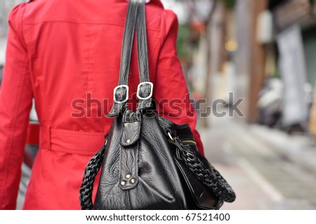 Single woman holding bag and walking in street, closeup portrait of shallow DOF. - stock photo