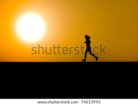 Single woman jogger in dramatic silhouette with large sun - stock photo