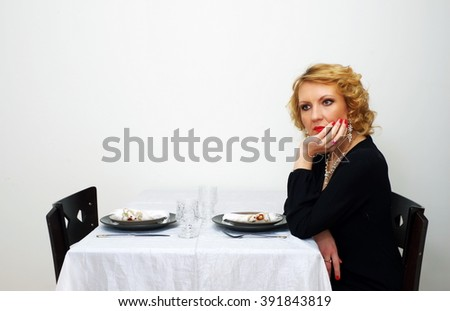 single woman sits besides served table - stock photo