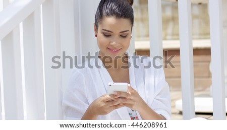 Single woman sitting near fence using smart phone