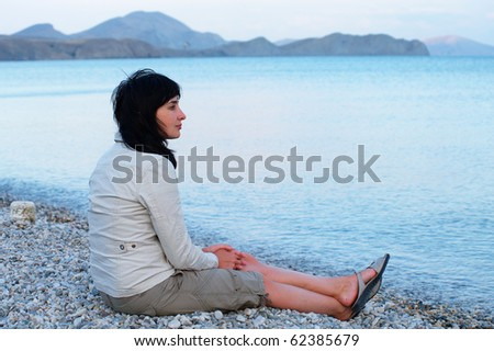 Single woman sitting on the empty beach relaxing - stock photo