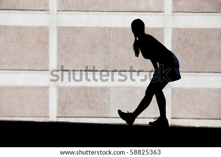 Single woman stretches before she goes for run. - stock photo