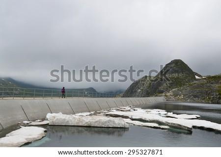 Single woman walking on high mountain dam wall in a cloudy day - stock photo