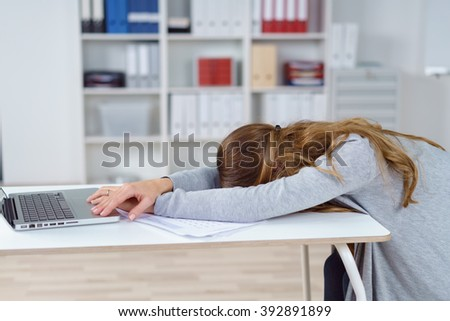 Single woman with long brown hair and gray sweater asleep at desk in front of laptop and papers in office with copy space - stock photo