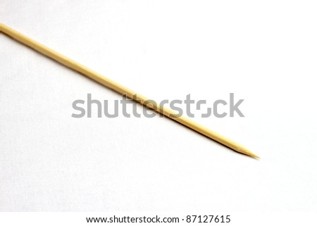 Single wooden bamboo skewer laying on white background