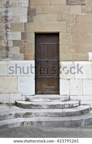 Single wooden door in the front of an old building at the top of a set of semi-circular stairs.