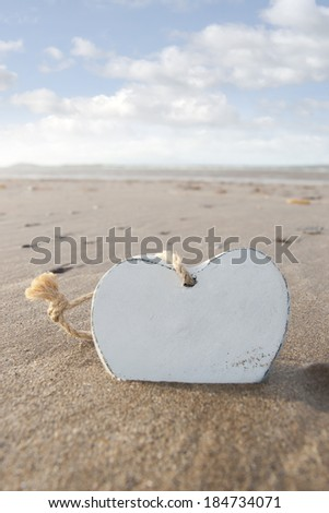 single wooden love heart in the sand on a wild Atlantic way Irish beach in summer with copy space - stock photo