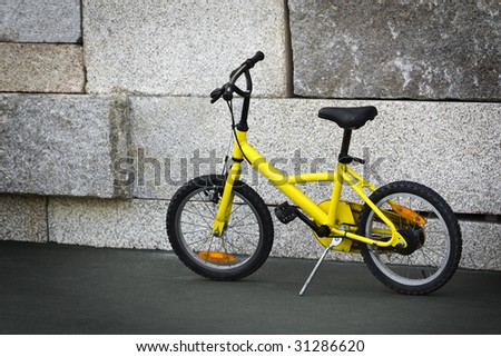 Single yellow bicycle on walkway against a stone wall