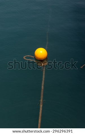 Single yellow buoy on calm blue sea water surface - stock photo
