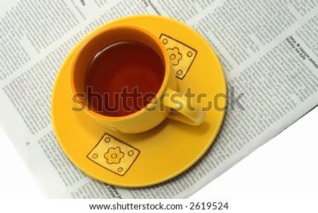 Single yellow tea cup on a newspaper - stock photo