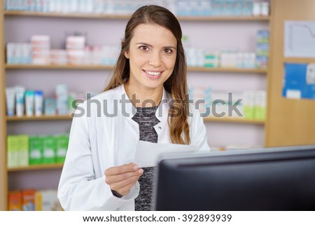 Single young pharmacy technician in long brown hair and white lab coat entering prescription order on computer with medications on shelf in background - stock photo