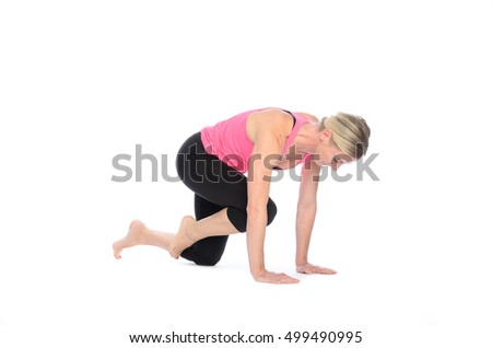 Single young woman in pink and black performing abdominal muscle exercises over white background