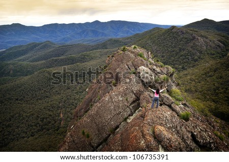 Single young woman looks out with determination on a mountain top - stock photo