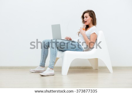single young woman sitting on a white chair with laptop in an empty room being happy, thinking on something - stock photo