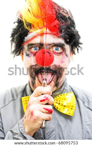 Sinister Clown Holds Up A Knife Vertical To His Face While Opening His Mouth In A Creepy Isolated Expression - stock photo